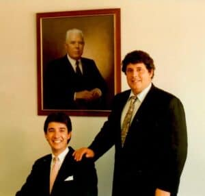 Current owners with founder portrait