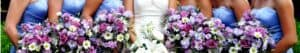 A bride's bouquet surrounded by her bridesmaids holding theirs. Vibrant colors.